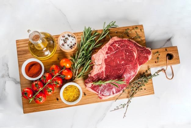 Carne crua fresca, bife de mármore de carne de cordeiro em uma placa de corte, com ingredientes para cozinhar. na mesa de mármore branca, vista superior copyspace