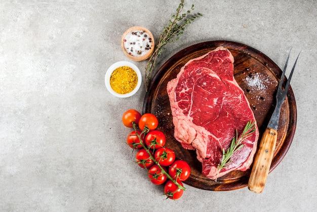 Carne crua fresca, bife de mármore de carne de cordeiro em uma placa de corte, com ingredientes para cozinhar. na mesa de pedra cinza, vista superior