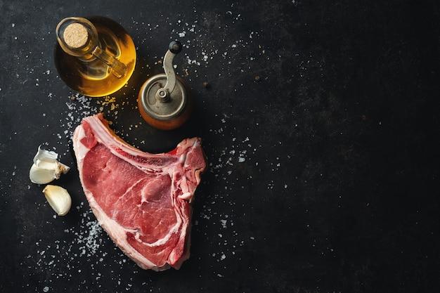Carne crua fresca com especiarias e sal em rústico escuro.
