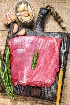 Carne crua fresca de flanco ou bavette bife de carne marmorizada com alecrim. fundo de madeira. vista do topo.