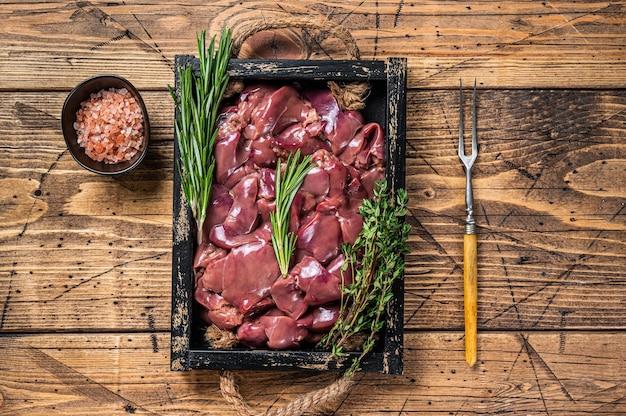 Carne crua fresca de miudezas de fígado de frango em uma bandeja de madeira