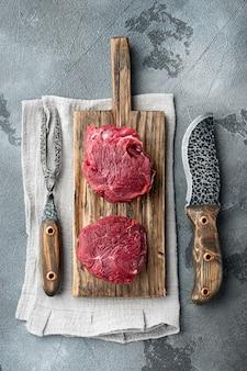 Carne crua fresca em mármore conjunto de filé mignon de bife, na tábua de madeira, na mesa de pedra cinza, vista de cima plana