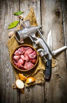 Carne crua fresca em uma cebola com picador, faca e especiarias em tecido velho
