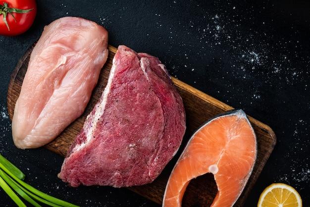 Carne crua fresca, filé de salmão e frango em fundo preto com especiarias. alimentos naturais ricos em proteínas. vista do topo.