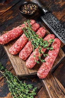 Carne crua homamade salsichas de lula kebabs em uma tábua de cortar