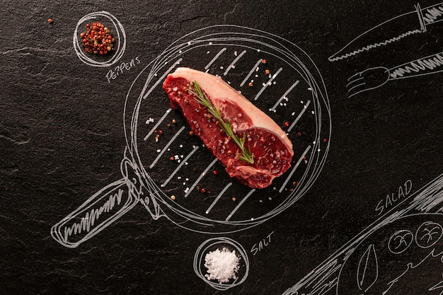 Carne crua na lousa preta com panela pintada e ingredientes. vista do topo. churrasco.