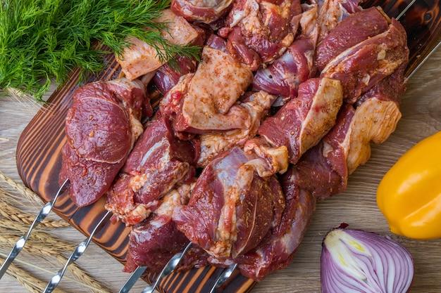 Carne crua no espeto em marinada com legumes e especiarias. vista do topo.