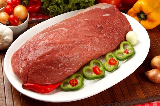 Carne crua no prato com legumes.
