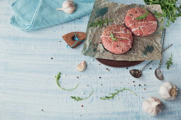 Carne crua orgânica envolvida nas tiras do bacon.