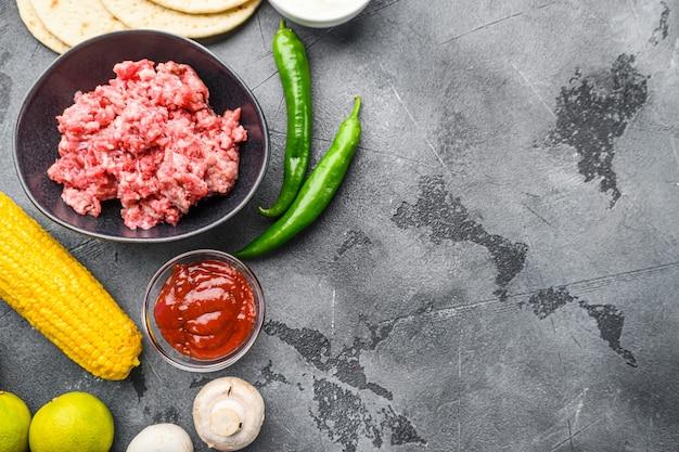 Carne crua orgânica picada para tacos mexicanos com culinária de legumes com ingredientes em uma tigela preta, sobre plano de fundo texturizado cinza, vista superior com espaço para texto.