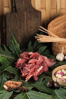 Carne crua ou cordeiro acima da folha de mamão, papaína enzim torna a carne tenra. preparação para cozinhar, gule, gulai, sate (satay) ou curry indonésio para o menu eid al adha