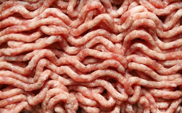 Carne crua picada e porco picado em moedor de carne, plano de fundo de alimentos close-up