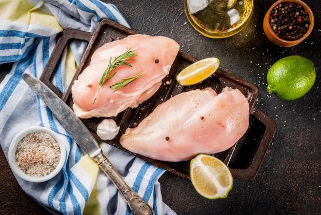 Carne crua pronta para filé de peito de frango grelhado ou churrasco com azeite de ervas e especiarias em fundo enferrujado escuro