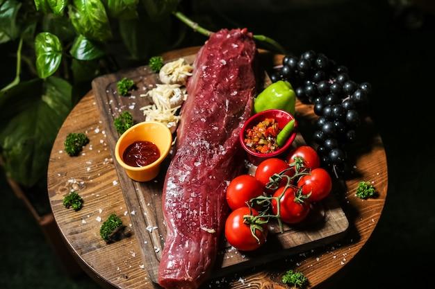 Carne crua salgada na placa de madeira com legumes cogumelos pimentão molho de tomate uva vista lateral