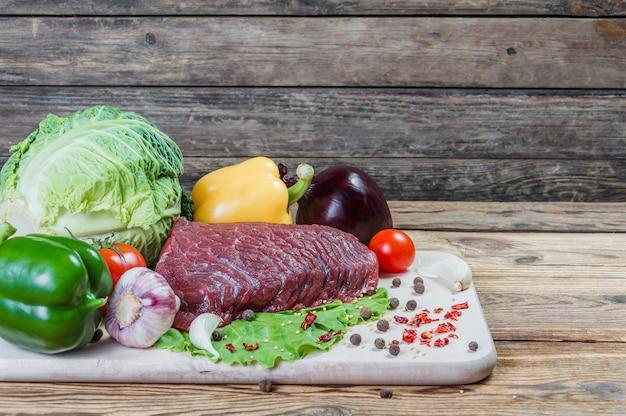 Carne crua, temperos e vegetais em uma placa de madeira rústica