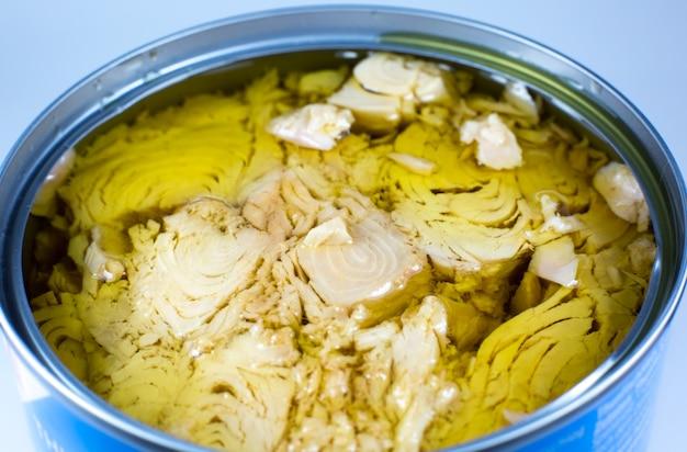 Carne de atum enlatada em óleo sobre fundo branco. lata aberta, foto de perto.