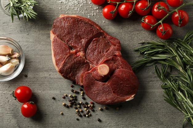 Carne de bife crua fresca, ervas e especiarias em cinza