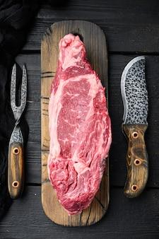 Carne de boi de lombo cortada em conjunto cru, em mesa de madeira preta, vista de cima plana lay