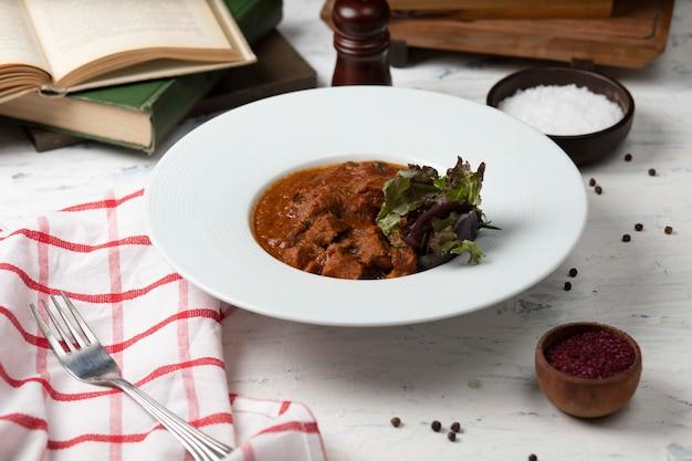 Carne de borrego refogada, guisado em molho de tomate e browh, servido com legumes e sumakh.
