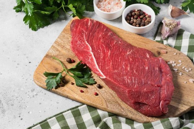 Carne de bovino crua em uma placa de madeira sobre uma mesa de cozinha cinza
