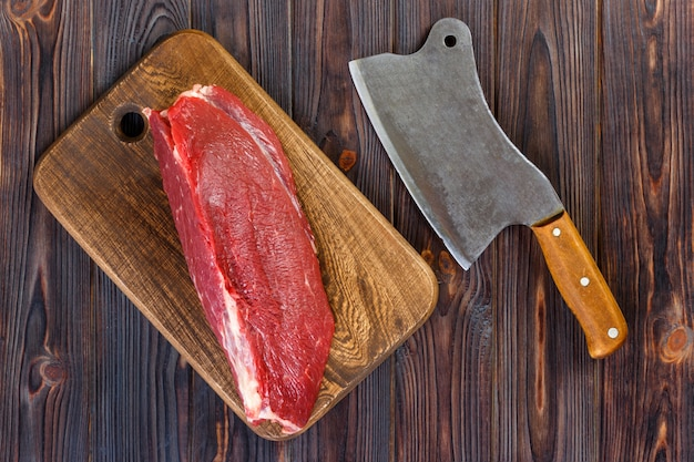 Carne de bovino crua na tábua com o velho cutelo vintage