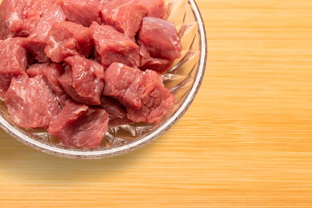 Carne de bovino em cubos crua fresca em um prato de vidro na tábua