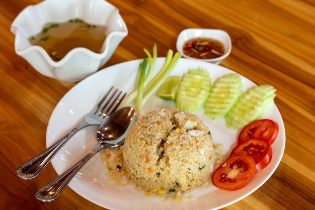 Carne de caranguejo frito, arroz e vegetais em uma mesa de madeira.