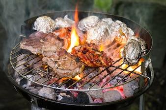 Carne de carne apetitosa deliciosa fresca na grelha cozinhando em fogo aberto na grelha da grade. Fundo de Natureza. Fechar-se.