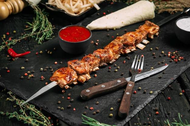 Carne de carneiro apetitosa com espetos de ossos com molho vermelho e cebola em conserva em um quadro negro
