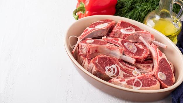 Carne de carneiro crua fresca no osso com ingredientes para marinar. copyspace