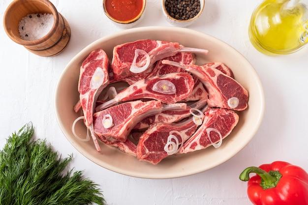 Carne de carneiro crua fresca no osso com ingredientes para marinar e cozinhar. vista do topo