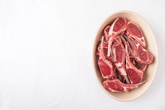 Carne de carneiro crua fresca no osso. costelas de carne de cordeiro não cozidas. . copie o espaço. vista do topo