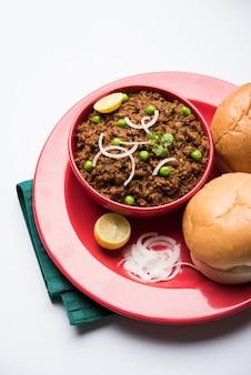 Carne de carneiro kheema pav ou carne picada picante indiana servida com pão ou kulcha, guarnecida com ervilhas verdes. fundo temperamental. foco seletivo