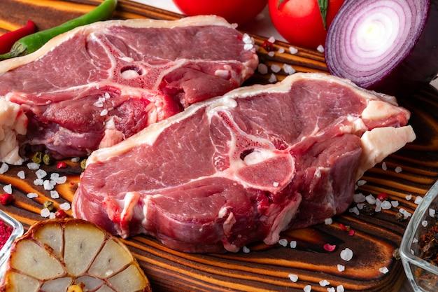 Carne de cordeiro crua em uma tábua de madeira com especiarias e legumes frescos