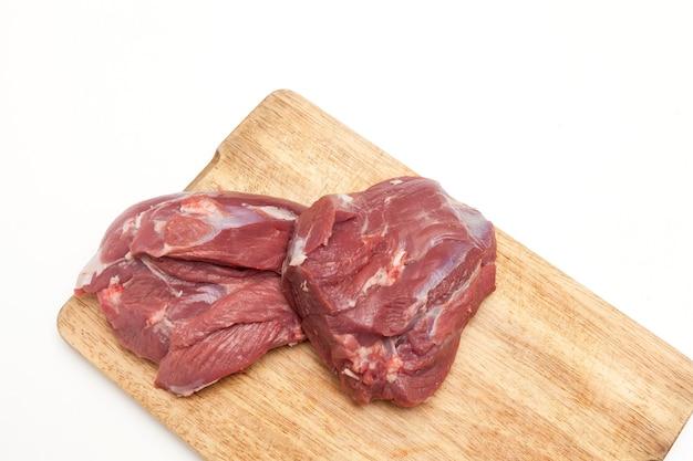 Carne de cordeiro crua fresca na tábua de madeira, vista superior, espaço de cópia.