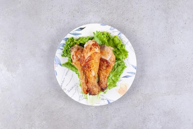 Carne de coxa de frango grelhado com alface em prato branco