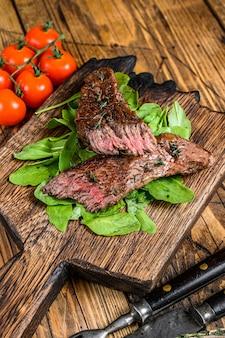 Carne de facão de carne grelhada saia cortada bife em uma placa de corte. fundo de madeira. vista do topo.