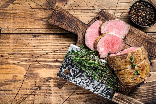 Carne de filé de lombo assado em uma placa de madeira com ervas. fundo de madeira escuro. vista do topo. copie o espaço.