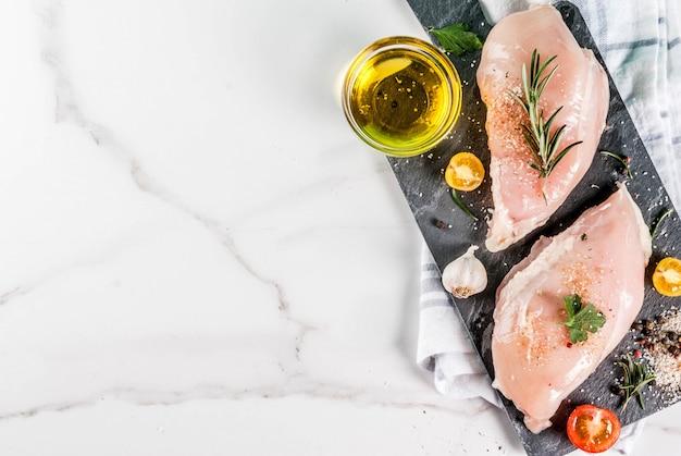 Carne de filé de peito de frango cru com especiarias e azeite de vista superior, copie o espaço