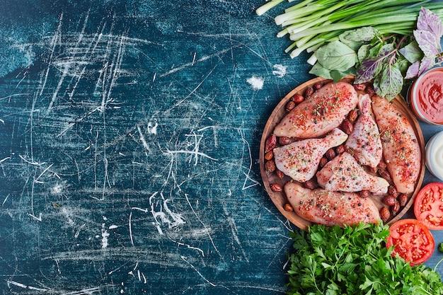 Carne de frango com especiarias vermelhas e vegetais ao redor.