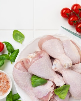 Carne de frango crua, pronta para grelhar ou assar as pernas, com tomates, ervas e especiarias na parede da mesa da cozinha branca clara. vista do topo.