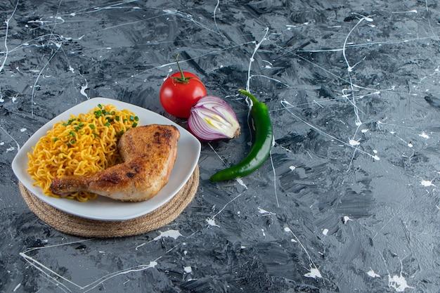 Carne de frango e macarrão em um prato sobre um tripé ao lado de vegetais, no fundo de mármore.