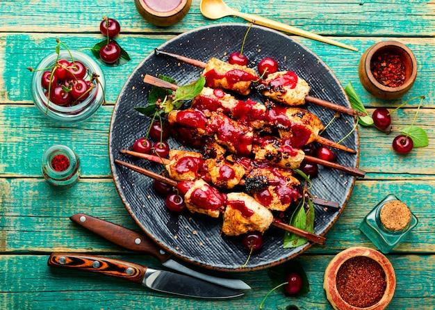 Carne de frango em espetos de madeira com molho de cereja. espetos de frango.