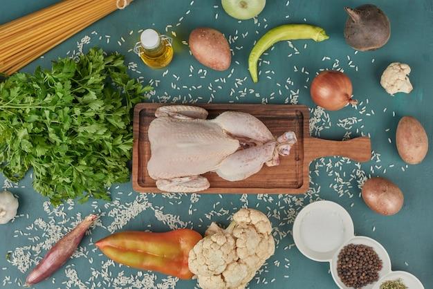 Carne de frango em uma placa de madeira com macarrão e legumes ao redor.