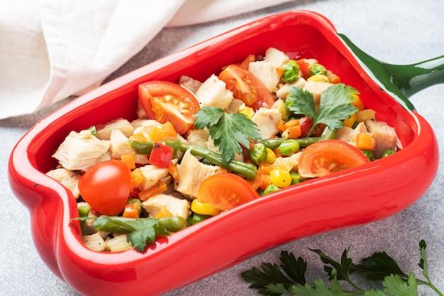 Carne de frango estufado com legumes cenouras pimentas ervilhas milho em um prato em forma de pimenta vermelha. copie o espaço.