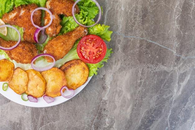 Carne de frango frito, batatas e legumes em um prato, no fundo de mármore.
