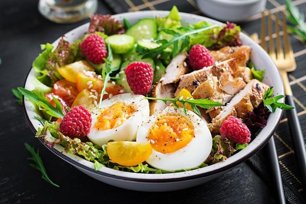 Carne de frango grelhado e salada de legumes fresca de tomate, pepino, ovo, alface e framboesa. dieta cetogênica. prato de tigela de buda em fundo escuro