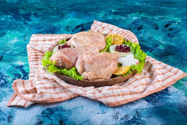 Carne de frango, limão, arilos de romã em um prato de madeira sobre o pano de prato