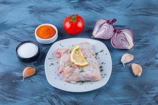 Carne de frango marinada e limão em um prato ao lado de alho, cebola, tomate e tigelas de temperos na superfície azul