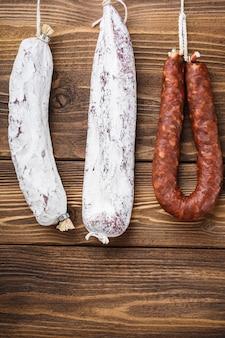 Carne de linguiça defumada espanhola tradicional pendurada na mesa de madeira.